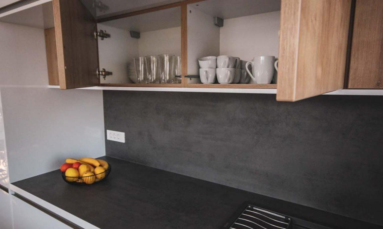 Moderna bela kuhinja s črnimi delovnimi površinami